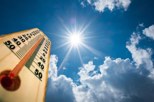 A thermometer shows high temperatures against the sun, a blue sky and a few white clouds.