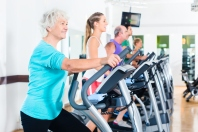Group of people on elliptical trainer exercising in gym